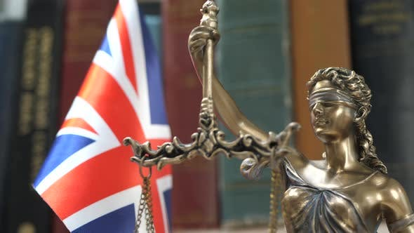 Thumbnail for Statue of Lady Justice with Bookshelf with Books and UK Flag Background
