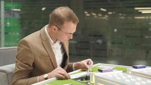 Male Architect with Plan on Paper, Stationery and 3d Building Model