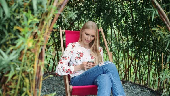 Thumbnail for Young Woman Using Smartphone in Plant Gazebo.