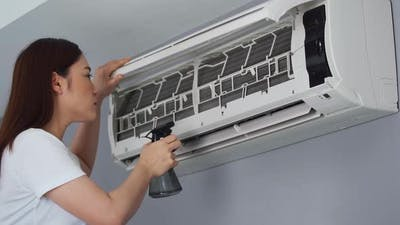 young woman cleaning the air conditioner indoors at home