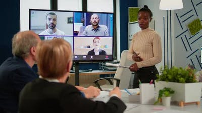 African Woman Discussing with Remote Managers on Video Call
