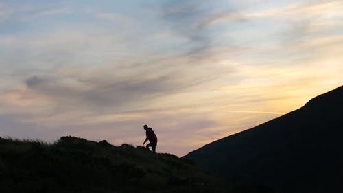 Dark silhouette of a hiker climbing a mountain at sunset and raising his hands reaching summit