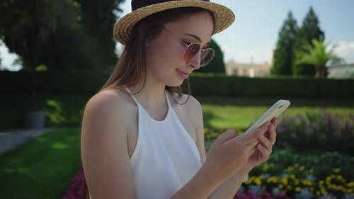 Woman with Smartphone in Garden of Lednice Palace