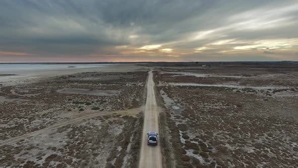 Car Going on Dirt Road on Flat Terrain at Sunset. Finish and The End