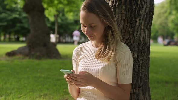 Cover Image for Close Up of a Beautiful Young Woman, That Is Using an Application in Her Smart Phone in Park