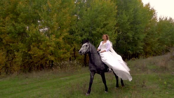 Thumbnail for Gorgeous Fiancee in White Dress Is Riding Horse Along Forest