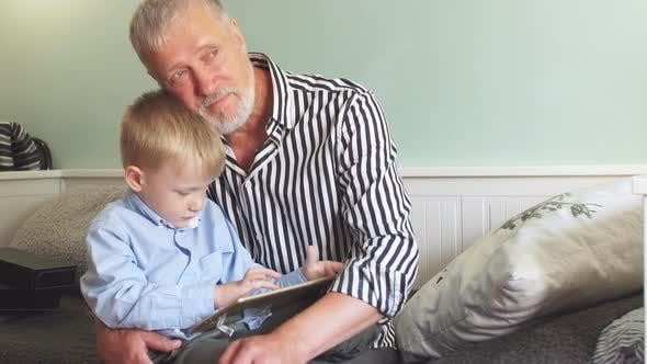 Thumbnail for Dreamy Grandpa Hugs Playing on the Tablet of a Grandson