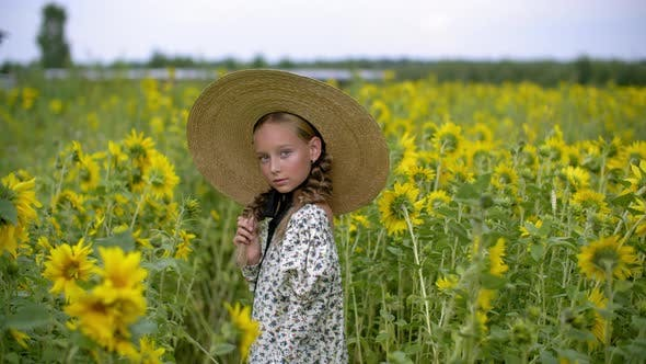 Thumbnail for Beautiful Teen Girl in Hat with Two Braids on Sunflowers Meadow in Countryside. Attractive Young