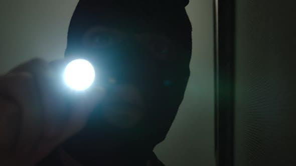 Dieb klettert ins Haus, glänzt eine Taschenlampe auf dem Bild und in eine Überwachungskamera