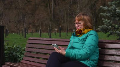 Senior Woman with Mobile Sitting on the Bench Outside