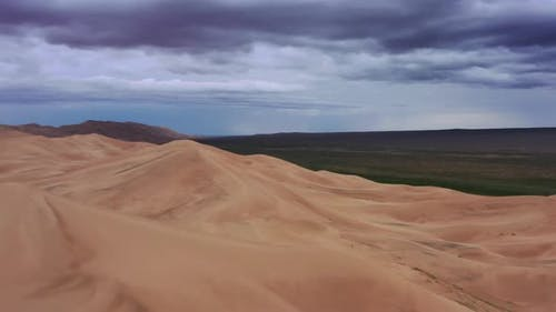 Sanddünen mit Sturmwolken in der Wüste Gobi