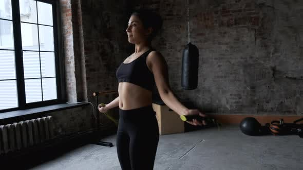 An attractive and athletic girl jumping rope, she is engaged in cardio exercises in gym