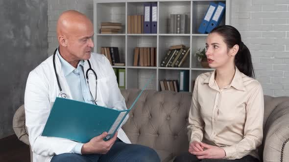 Young Hispanic Woman Looking Test Results Male Senior Doctor