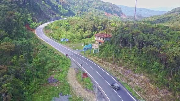 Thumbnail for Flying Camera Shows Car Driving Along Mountain Road and Motel