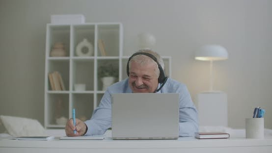 Thumbnail for Cheerful Man Is Chatting with Colleagues By Video Chat on Laptop During Daily Online Meeting and