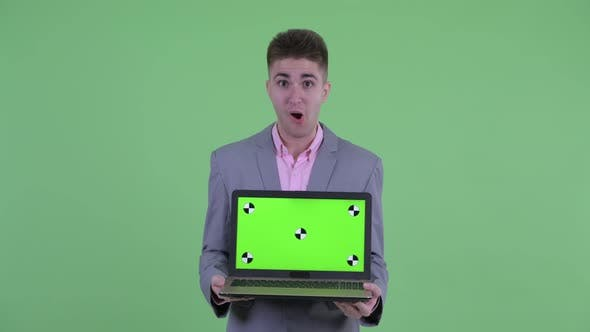 Thumbnail for Happy Young Businessman Showing Laptop and Looking Surprised