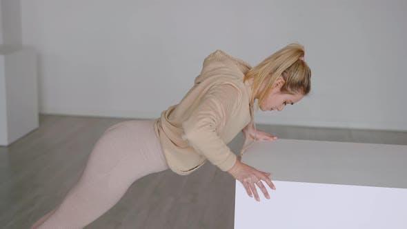 Blond Sportswoman Doing Push Ups on Cube