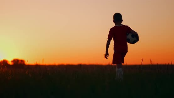 Thumbnail for A Boy with a Soccer Ball Goes Into the Field and Looks at the Sunrise.