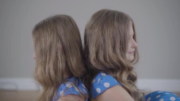 Thumbnail for Identische kaukasische Zwillingsschwestern sitzen zurück an Rücken drinnen. Kamera bewegt sich von rechts nach