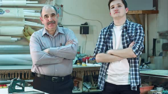 Thumbnail for Portrait of Two Workers, Standing in Workshop and Looking at Camera Seriously