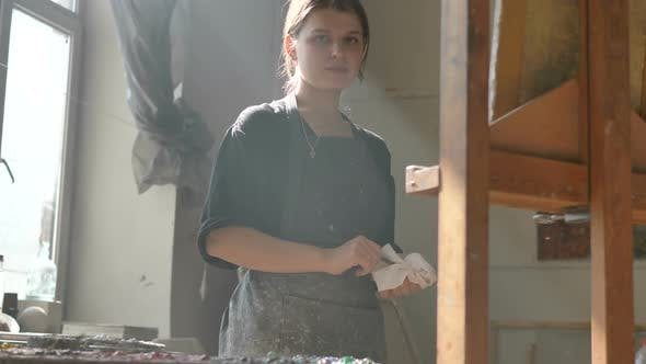 Thumbnail for Positive Woman Holds Napkin and Brush Standing Near Easel