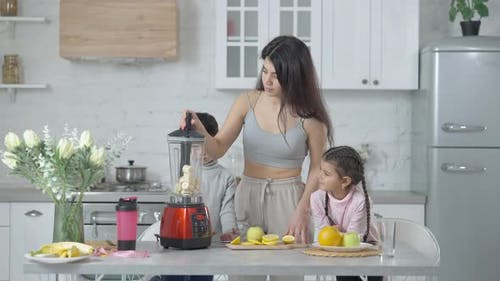 Young Middle Eastern Mother Turning on Blender Talking with Son and Daughter Standing in Kitchen