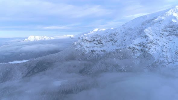 Thumbnail for Frozen mountain top in sunny winter day, fog covering bottom side of mountain