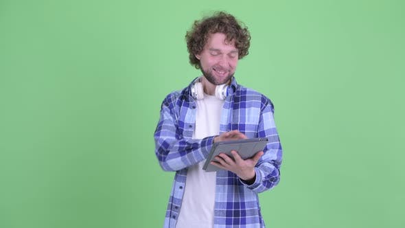 Cover Image for Happy Young Bearded Hipster Man Thinking While Using Digital Tablet
