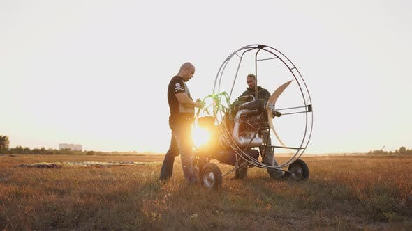 Thumbnail for Motor Paraglider Stands in a Field at Sunset with a Wooden Propeller, Two Pilots Warm Up the Engine