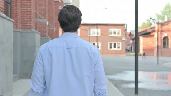 Back View of Man Walking in Empty Street