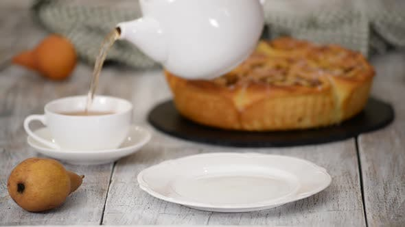 Thumbnail for Unrecognizable Person Pouring Fresh Hot Tea Into Cup on Table and Put Bun on White Plate.