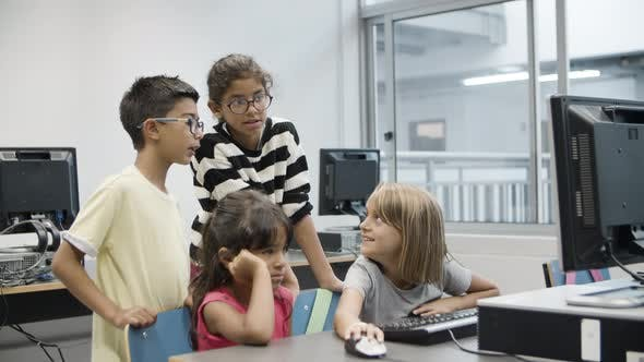 Excited Multiethnic Children Looking at Computer Monitor