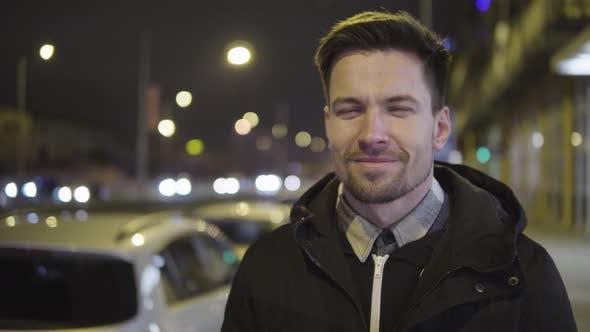 Thumbnail for Ein junger hübscher Mann lächelt bei Nacht in einer Straße in einem urbanen Gebiet vor der Kamera - Nahaufnahme