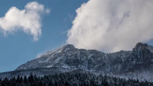 Dramatic fast moving clouds pass over a snowy  mountain,