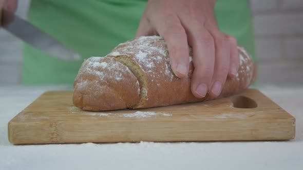 Cut a loaf with knife.