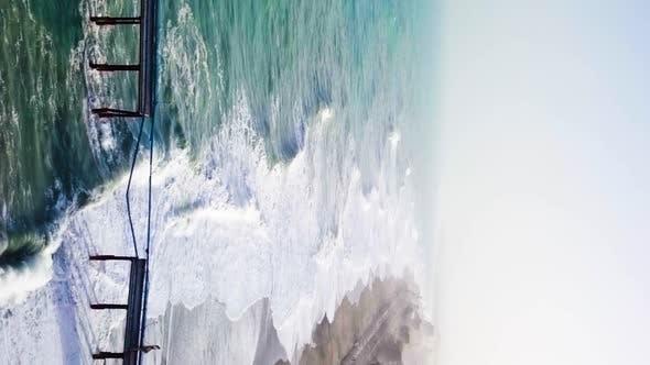 Vertical video of stormy ocean and pier