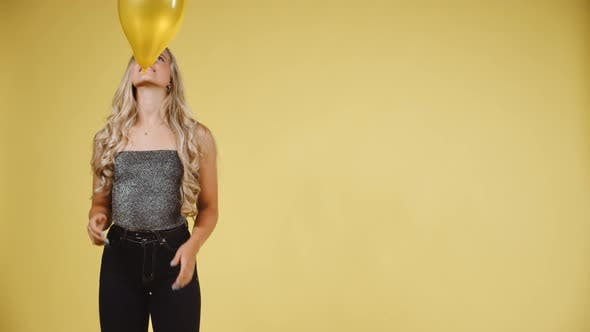 Thumbnail for Sexy Model Throwing and Catching a Yellow Ballon Against Yellow Background