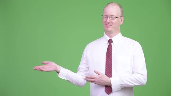 Thumbnail for Happy Mature Bald Businessman Showing Something