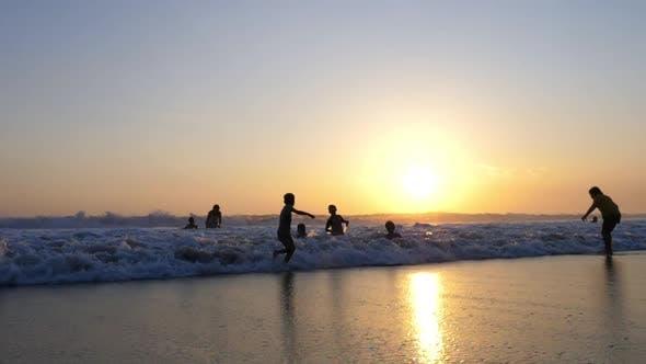 Kinder spielen am Strand mit Wellen bei Sonnenuntergang