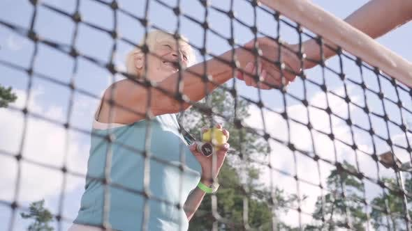 Adult Woman Shakes Hands with an Unrecognized Rival Standing on a Tennis Court