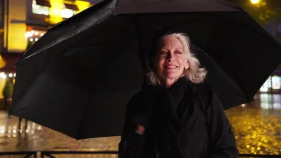 Thumbnail for Senior woman in Paris dancing under umbrella on rainy night in the city