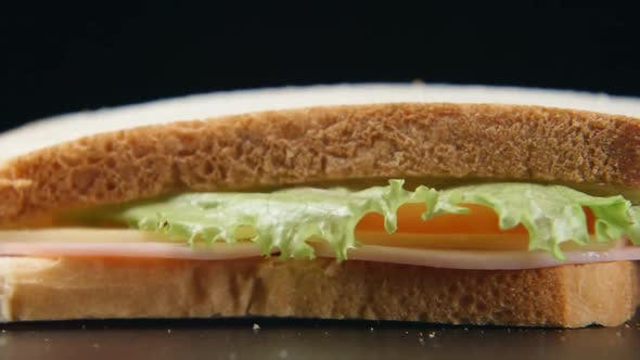 Sandwich falls on a black table - close up