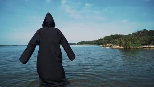 Terrible witch in black mantle in the water outdoor.