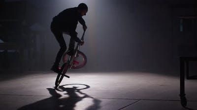 BMX rider doing tricks in dark warehouse.