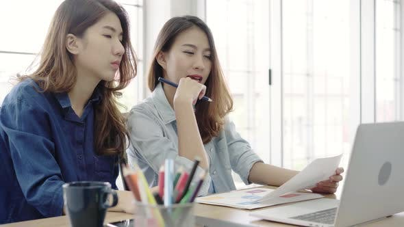 Asian business women in smart casual wear working on laptop while sitting on desk in office.