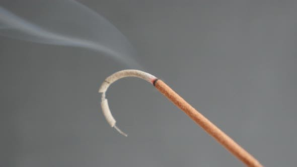 Burned  fragrant incense stick smoke spreading 4K 2160p 30fps UltraHD footage - Close-up of aromatic