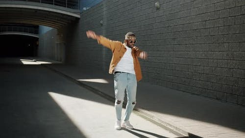 Looping of Cheerful African American Person Dancing Waving Arms Outdoors on Sunny Day