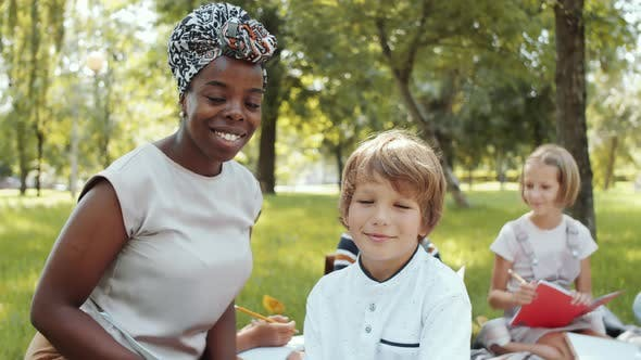 Joyous Multiethnic Teacher and Boy Posing for Camera during Outdoor Lesson