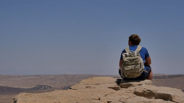 Thumbnail for Young man with backpack sitting on cliff's edge and enjoying