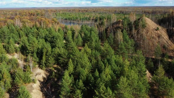 Flying above the abandoned quarry with forest and lake in autumn